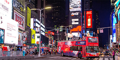 a TopView Double Decker Bus in Time Square at Night